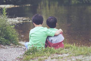 hermanos abrazados viendo el rio