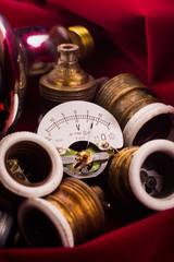 old voltmeter, screwed lamp sockets  and red lamp on red velvet