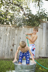 Two brothers playing in a garden with a water-filled tub and hose.