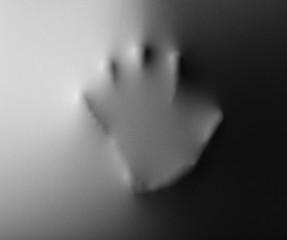 Hand pressing through fabric as horror background
