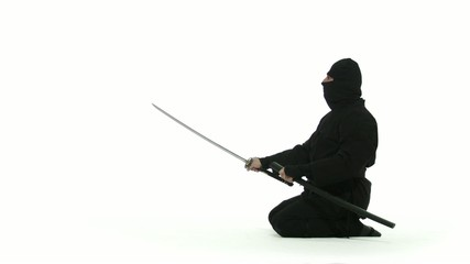 Seated assassin pulls out a long, curved sword and brandishes it, menacingly, then puts it away again.  Profile shot against white background.