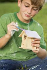 A boy in a garden, painting a bird house.