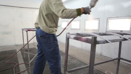 Man in protective clothes works in paint-spraying booth