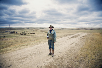 Man wearing cowboy hat and cowboy boots standing on a country lane in the Canadian Prairie.