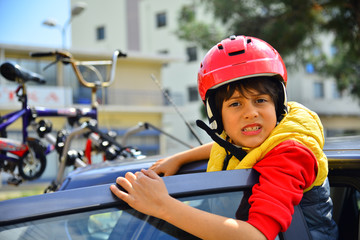 Boy with red helmet and a colorful bike