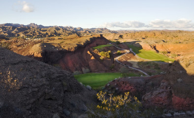 An elevated view over the mountain and desert landscape and golf course greens in the valley.