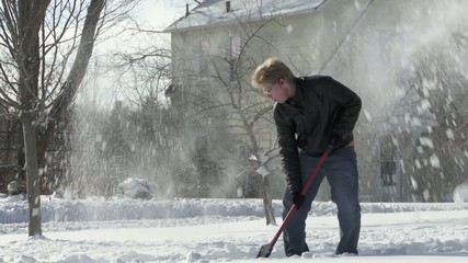 Teenager shovels snow quickly in the Mid West, USA.  Full length shot from side with camera movement.