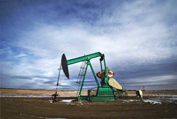 An oil pump jack at a drilling site for oil, an oil field in Saskatchewan.
