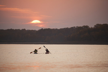 Two kayakers at sunset on a calm lake.