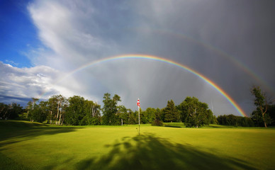 A rainbow in the sky above a golf green.