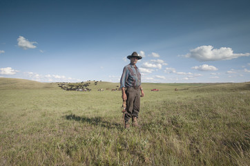 Spring roundup. A working cowboy on the plain. A herd of cattle.
