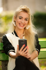 blonde woman with smart phone on a bench in park
