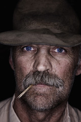A man in a battered hat, with blue eyes and a moustache, chewing a piece of straw. A cowboy.