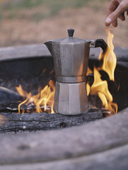 Espresso maker standing over an outdoor fire.