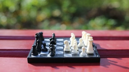Boy and girl hands move chess piece above chessboard