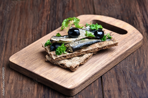 Sprats sandwich on wooden cutting board - 80135915