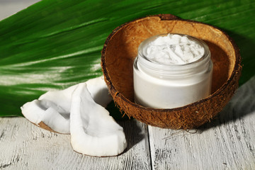 Fresh coconut oil in glass bottle and green leaf