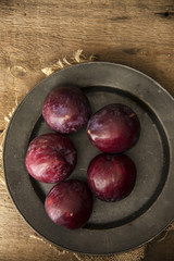 Fresh plums in natural light setting with moody vintage retro st