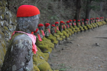 Row of Japanese Buddha wearing red scarf, Jizo statues