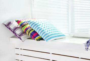 Colorful pillows on windowsill
