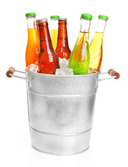 Glassware of different drinks in metal bucket with ice cubes