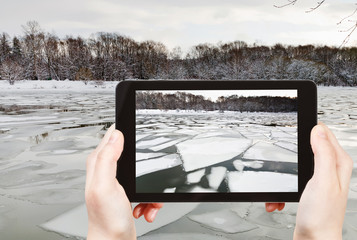 tourist photographs of floating of ice on river