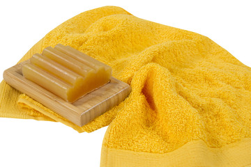 piece of soap and a yellow towel isolated on white background