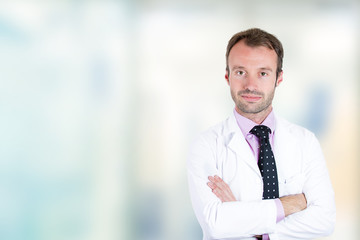 Confident male doctor smiling arms folded standing in hospital