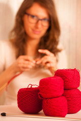 beautiful young woman knitting making handmade clothes