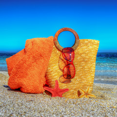 straw bag, beach towel and sunglasses on the sand