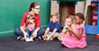 Kinder im Kindergarten schauen Bilderbuch an