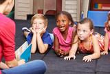 Fototapety Lachende Kinder im Kindergarten hören zu