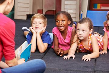 Lachende Kinder im Kindergarten hören zu