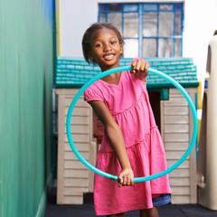 Afrikanisches Kind mit Reifen im Kindergarten