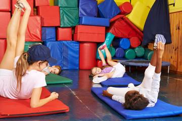 Kinder turnen im Kindergarten mit Erzieherin