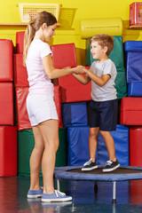 Kind hüpft auf Trampolin in Turnhalle