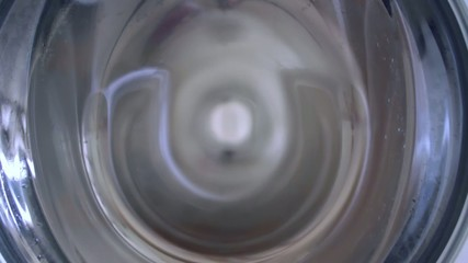 Tight shot of clothes being spun in washing machine.