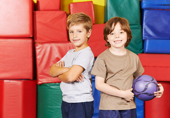 Zwei Kinder mit Ball in der Turnhalle