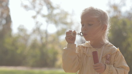 Little blonde girl blow bubbles on nature