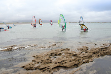 wind surfers braving the strong storm and rocks