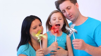 father, mother and daughter hold toy windmills turning from wind