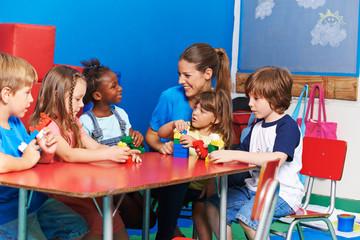 Kinder sitzen mit Erzieherin im Kindergarten