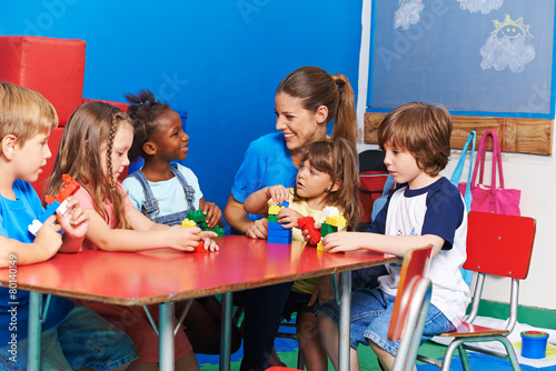 Leinwanddruck Bild Kinder sitzen mit Erzieherin im Kindergarten