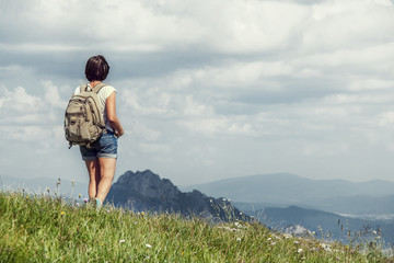 Woman walk on mountain hill in summer time