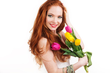 Beautiful redheaded smiling girl is holding tulips