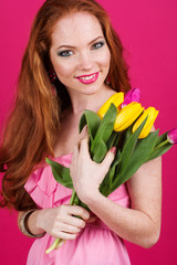 Beautiful redheaded girl is holding tulips, spring time