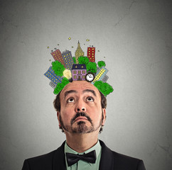 middle aged man looking up city plan above head