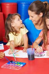 Kinder malen mit Wasserfarbe im Kindergarten