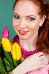 Beautiful redheaded girl is holding yellow tulips