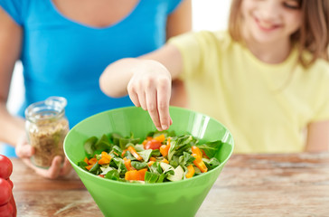 close up of happy family cooking salad in kitchen